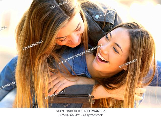Two funny affectionate friends joking and laughing together in the street