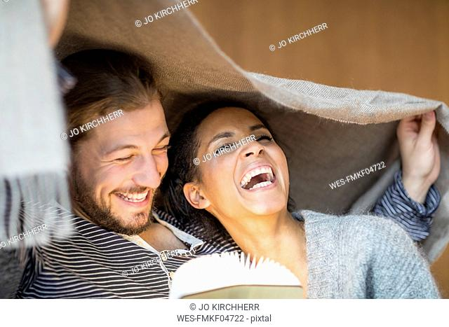 Portrait of laughing young couple at home
