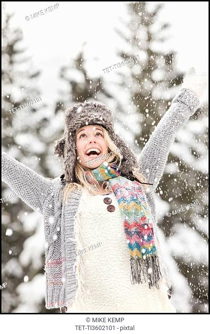 USA, Utah, Salt Lake City, young woman in winter clothing throwing snow in air