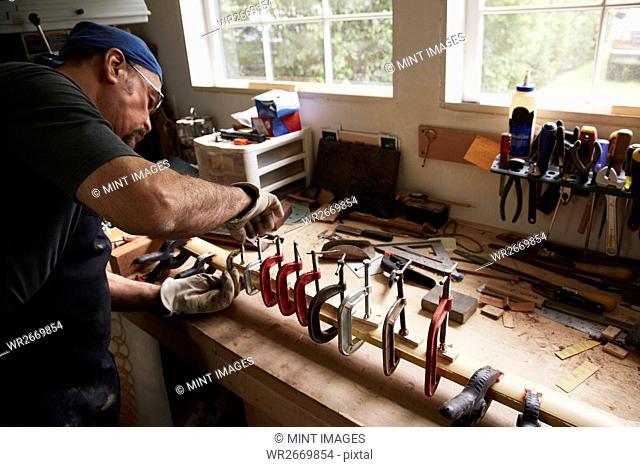 A bow maker working on a wooden bow in his workshop shaping the wood by holding it in clamps