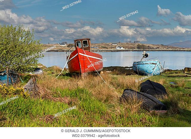 Ireland, Galway, 2016/04 , A red and blue derelict wooden fishing boats decaying on the shoreline of the Irish coast.