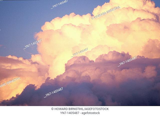 Billowing cumulus clouds threaten a storm as they glow orange in the late afternoon sun