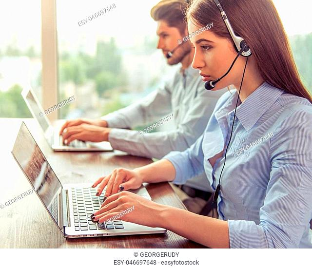 Side view of beautiful young business woman and handsome businessman in headsets using laptops while working in office