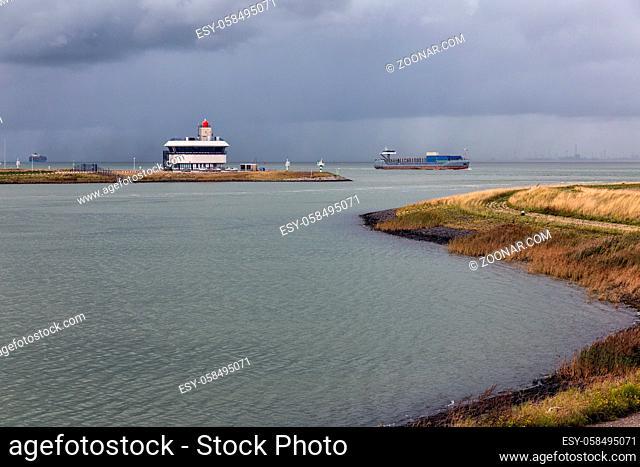 Entrance Dutch Canal Gent-Terneuzen and cargo ship sailing at river Schelde