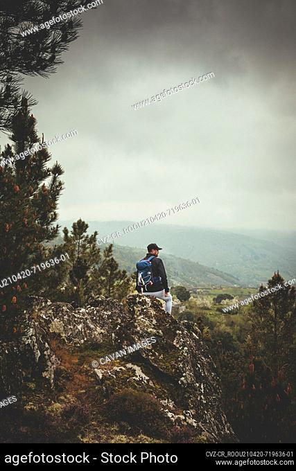 Man with backpack and cap on the mountain