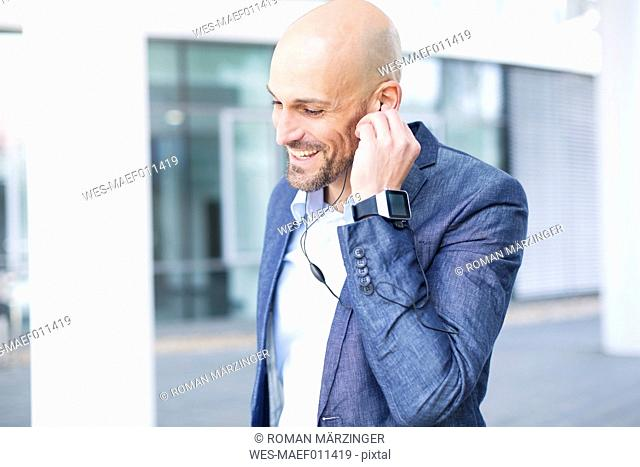 Smiling businessman with earbuds and smartwatch