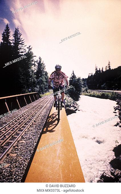 Mountain biker riding towards camera, crossing railway bridge