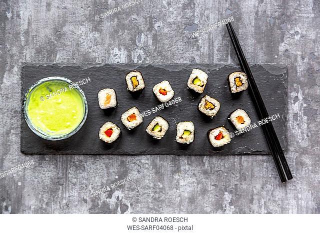 Sushi on slabe plate, wasabi in bowl, chop sticks
