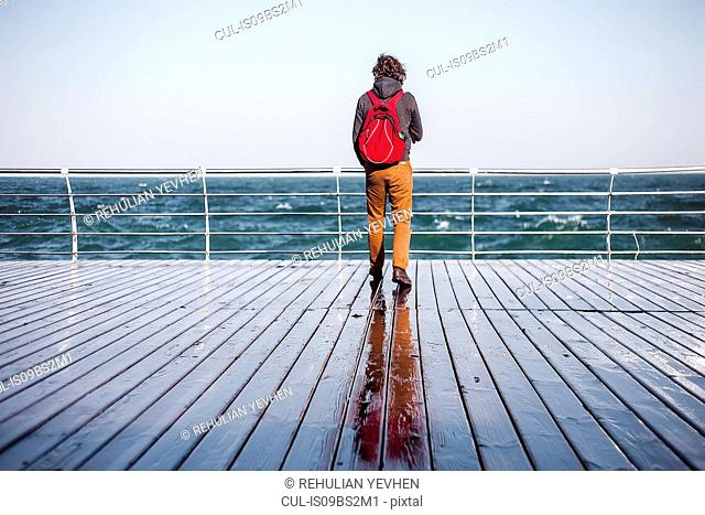 Mid adult man looking out from pier to sea, rear view, Odessa, Odeska Oblast, Ukraine