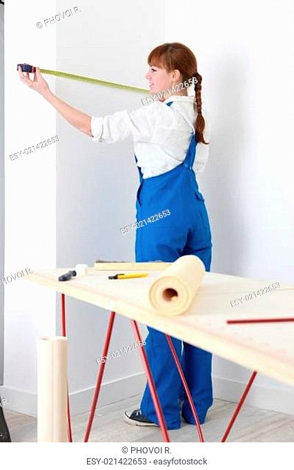 Female decorator measuring wall
