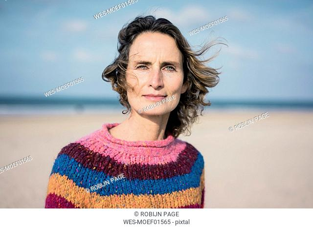 Mature woman enjoying the wind on the beach, portrait