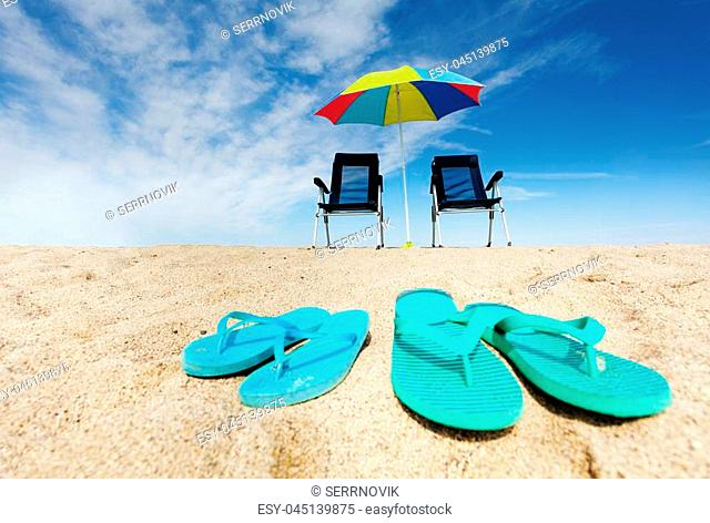 Tropical background with two pairs of flip flops, deck chairs and sun umbrella on the sandy beach