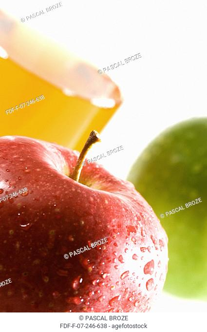 Close-up of a glass of apple juice and apples