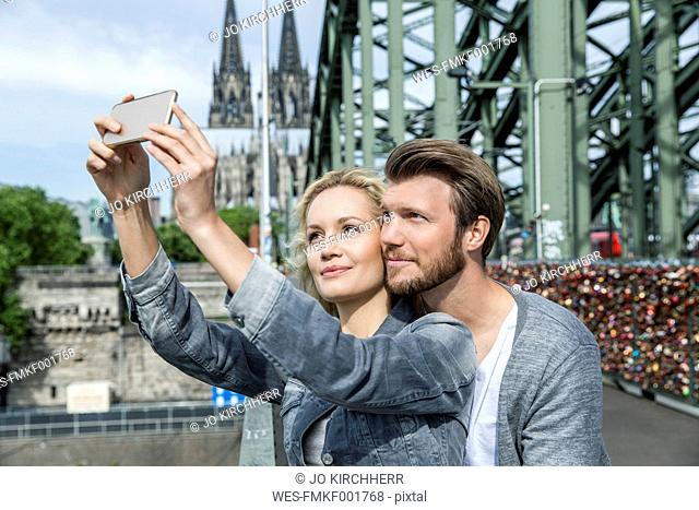 Germany, Cologne, young couple taking a selfie with smartphone at Hohenzollern Bridge