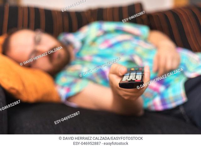 Man relaxing in sofa with remote control watching tv. Shallow dof focus on remote control