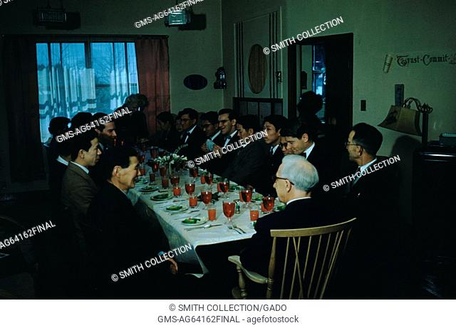 Missionaries at a seated dinner with Japanese congregants at a long rectangular table, serving plated salads, with red water glasses