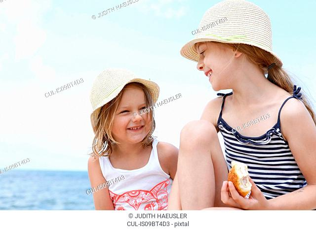 Two girls in sun hats eating sandwiches on beach, Scopello, Sicily, Italy
