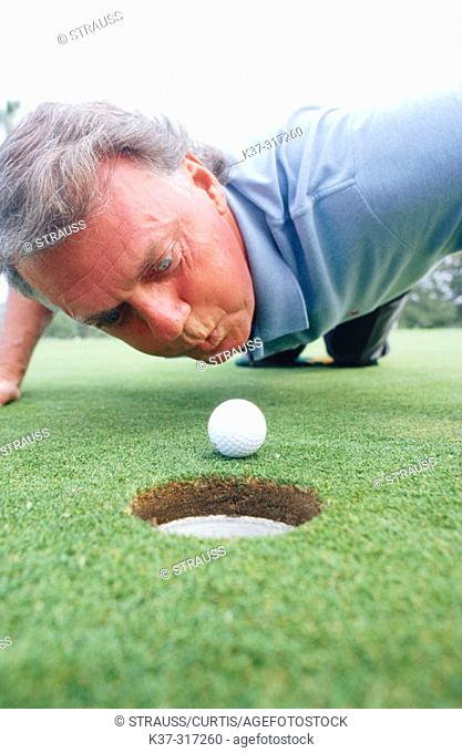 Frustrated man attempting to blow his golf ball into the hole