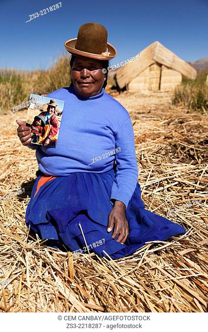 Aymara indigenous woman wearing a bowler hat holding her own photo in hand, Uros Islands, Lake Titicaca, Puno, Peru, South America