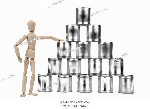 Wooden mannequin by a tin can pyramid, on white background, studio shot