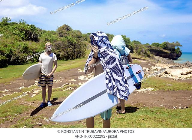 Three people with surfboards with one drying himself with a towel