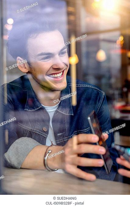Male student showing smartphone in cafe window seat, view through window