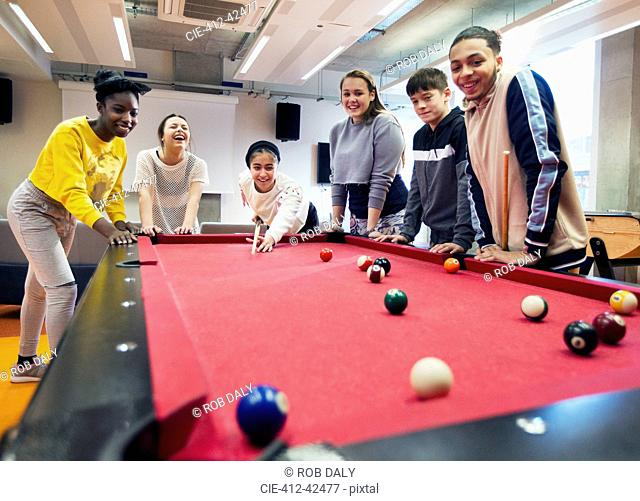 Teenagers playing pool in community center