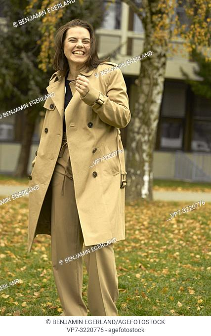 young happy laughing woman outdoors in park during autumn season, wearing coat, candid emotion, pure happiness, in Munich, Bavaria, Germany