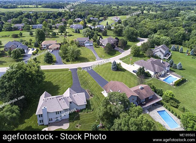 Aerial view of an upscale tree-lined neighborhood in a Chicago suburban city in summer