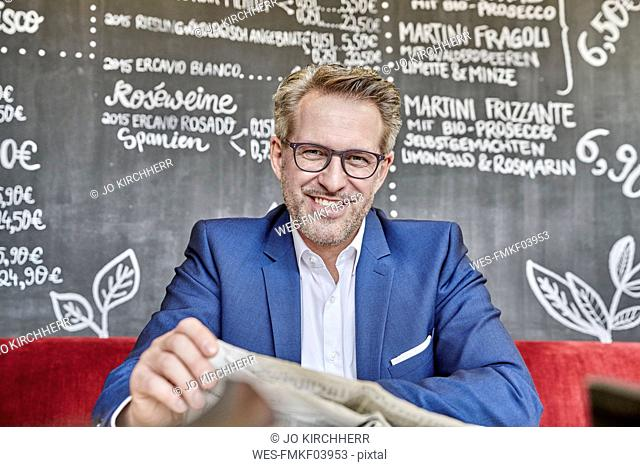 Portrait of smiling mature businessman in cafe reading newspaper