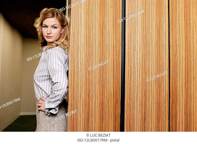 woman standing against wooden wall