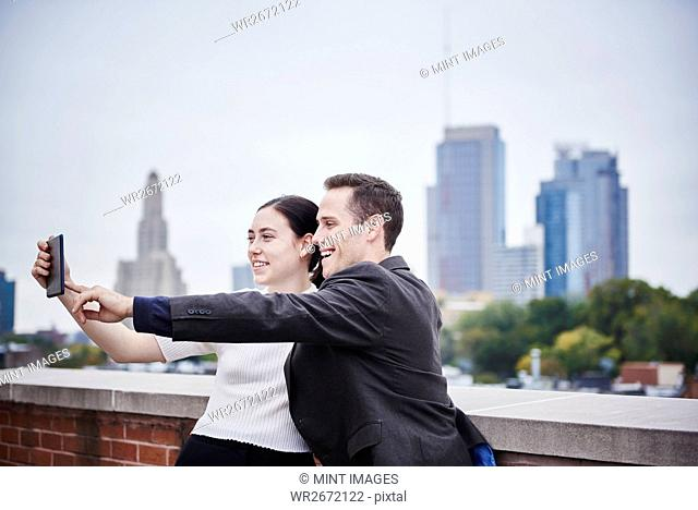 A young woman and a young man standing on a rooftop looking at a cellphone together
