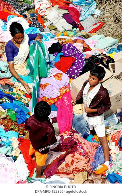 A woman selecting clothes from the stacks of clothes that arrived Nagapatinam following the Tsunami disaster as help from the people of the country as help for...