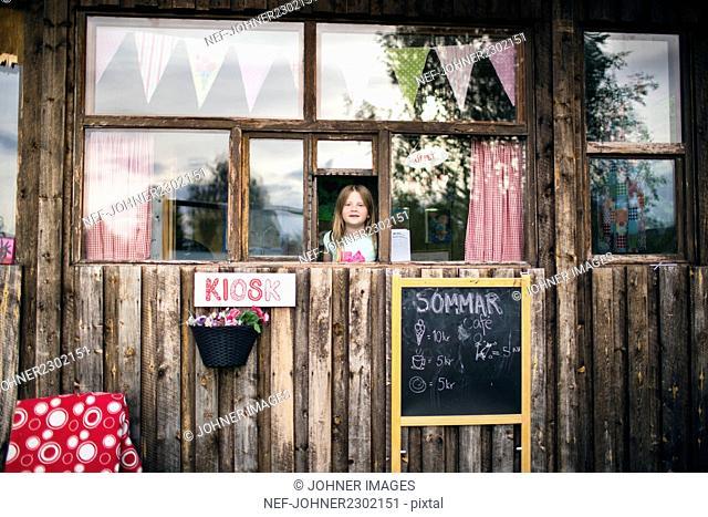 Girl looking through window of kiosk