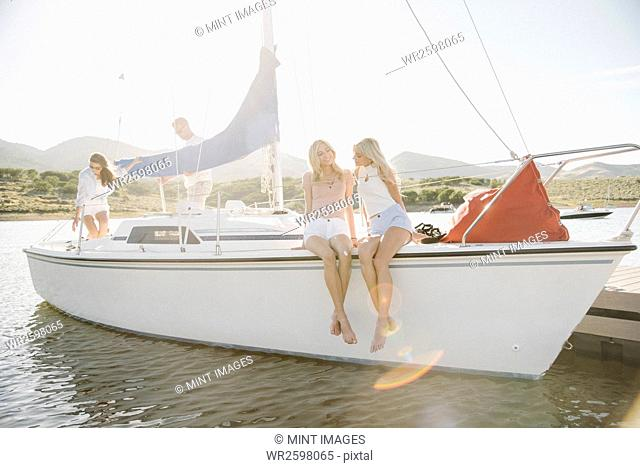 Two blond sisters sitting on a sail boat