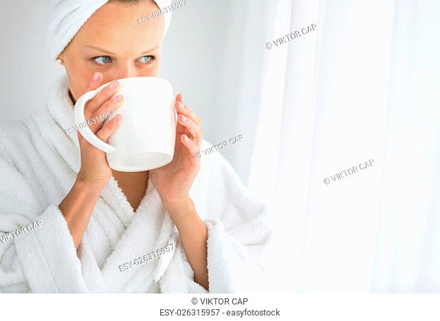 Gorgeous young woman wearing a bathrobe and enjoying a mug hot tea, savouring every sip (shallow DOF; color toned image)