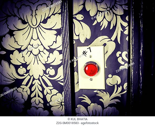Selective colour -- red button on a dark grey wall paper -- full color image simplified to two colors, Halifax, Nova Scotia, Canada
