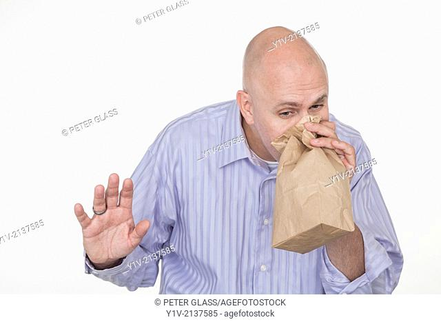 Middle-age bald man blowing into a paper bag