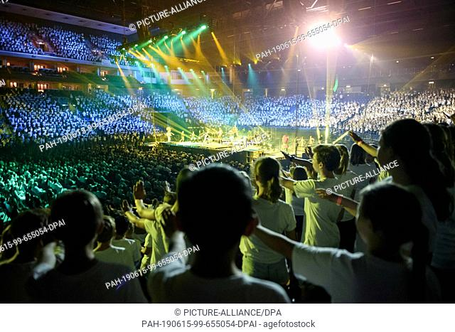 """14 June 2019, Berlin: Children and teenagers stand singing and dancing during the concert of """"""""6K United!"""""""" in the Mercedes-Benz Arena"""