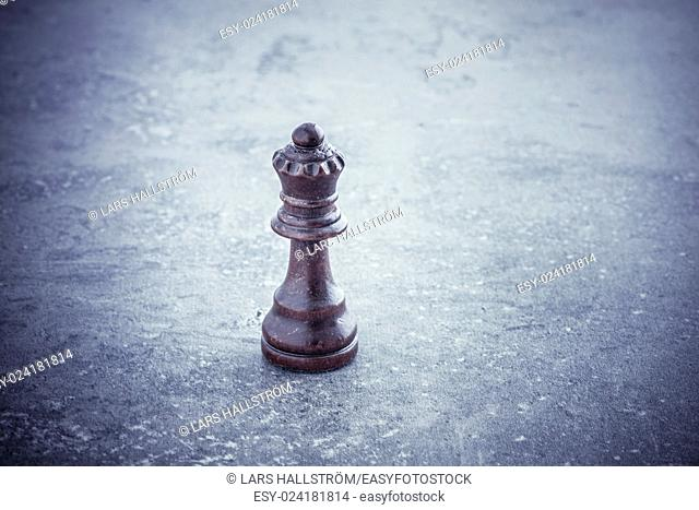 One black chess queen standing alone on stone table with copy space. Concept of strategy, competition and leadership