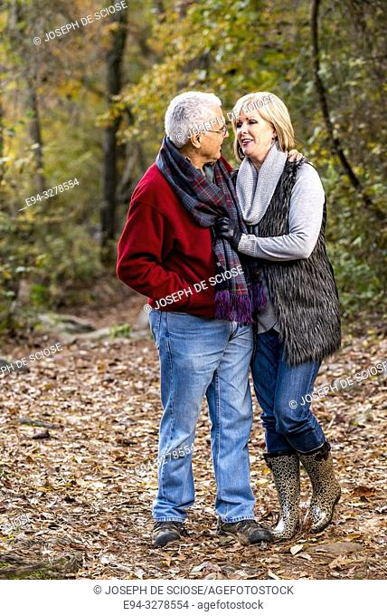 A happy 65 year old man and a 59 year old blond woman walking together and smiling at each other in a forest setting