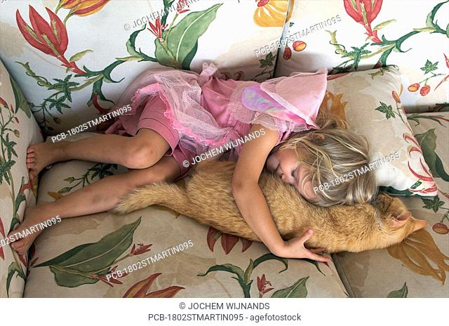 Four year old girl on the couch with her cat