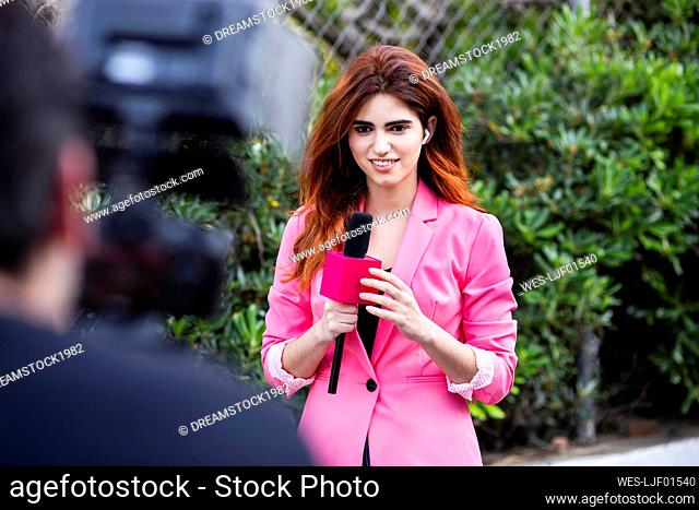 Man filming female reporter talking over microphone while standing outdoors