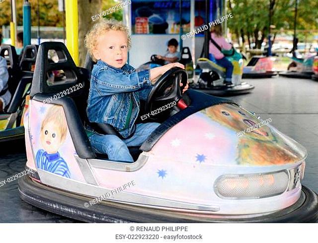 a little boy driving a bumper car
