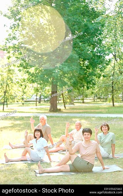 Portrait of content senior people sitting on mats in park and twisting body while practicing yoga at group class