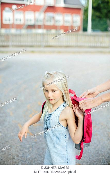 Girl putting backpack on