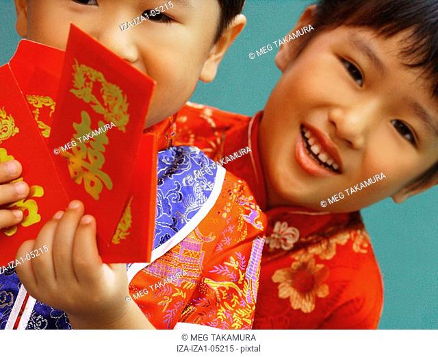 Close-up of a boy and his sister holding red gift packets Hong Bao