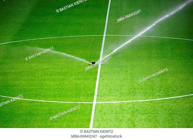 green lawn of a football field with irrigation plant