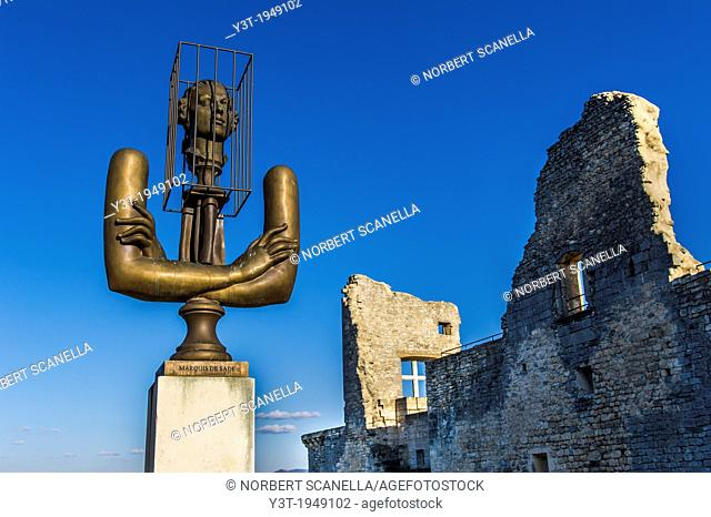 """Europe, France, Vaucluse, Luberon. The perched village of Lacoste. Sculpture of Alexander Burganov """"""""The Marquis de Sade"""""""" dedicated to Pierre Cardin in front..."""
