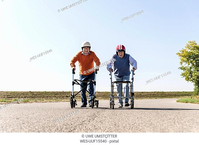 Two old friends wearing safety helmets, competing in a wheeled walker race